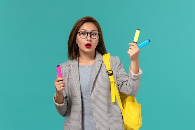 水色の壁にフェルトペンを保持している彼女の黄色のバックパックを身に着けている灰色のジャケットの女子学生の正面図