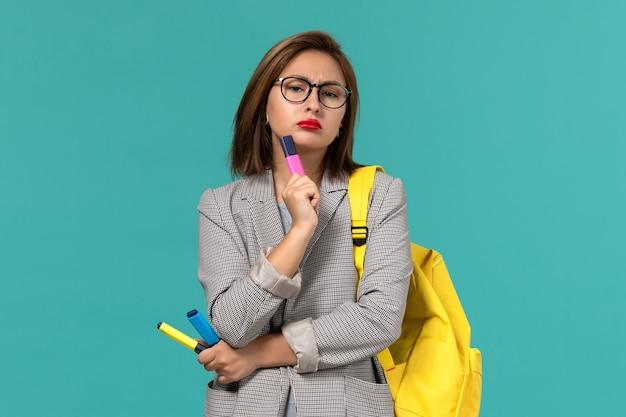 水色の壁に考えているフェルトペンを保持している彼女の黄色のバックパックを身に着けている灰色のジャケットの女子学生の正面図