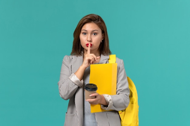 水色の壁にファイルとコーヒーを保持している彼女の黄色のバックパックを身に着けている灰色のジャケットの女子学生の正面図