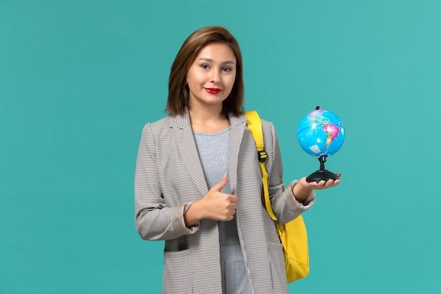 Вид спереди студентки в серой куртке в желтом рюкзаке с маленьким глобусом на голубой стене