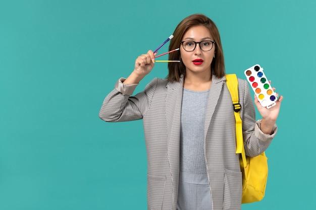 Вид спереди студентки в серой куртке в желтом рюкзаке с красками на синей стене