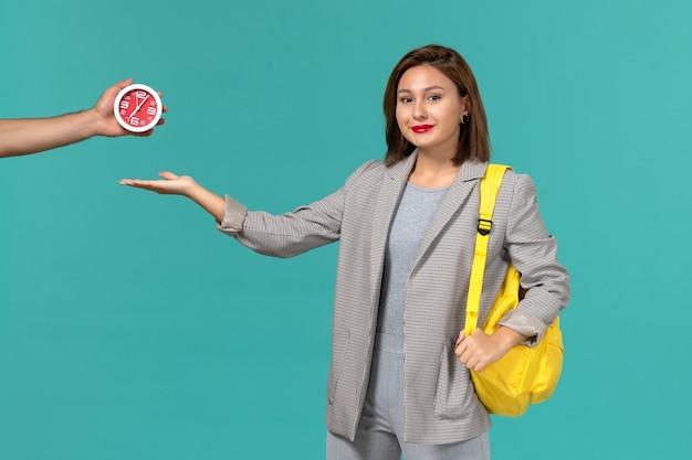黄色のバックパックを身に着けて、水色の壁に笑みを浮かべて灰色のジャケットの女子学生の正面図