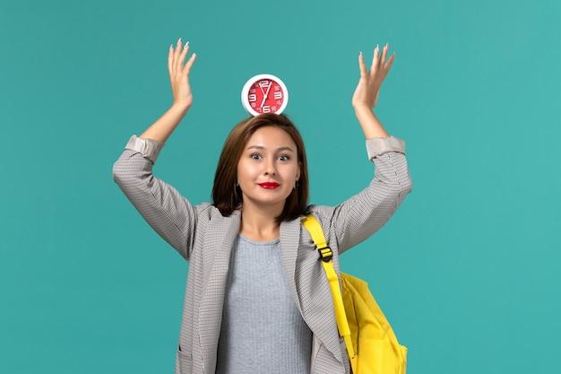 青い壁に彼女の頭に時計を保持している黄色のバックパックを身に着けている灰色のジャケットの女子学生の正面図