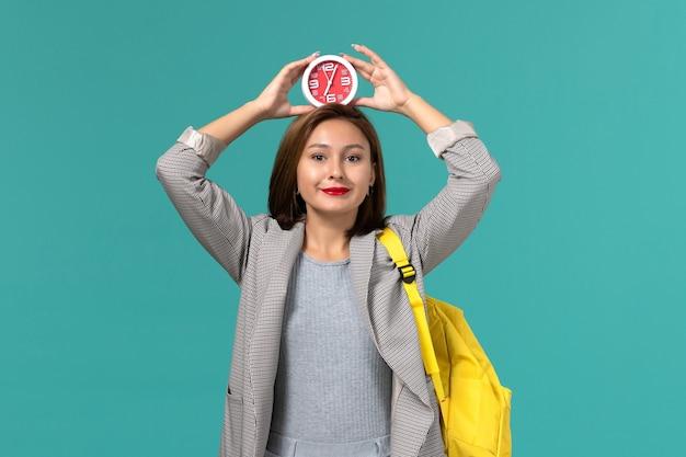 水色の壁に彼女の頭に時計を保持している黄色のバックパックを身に着けている灰色のジャケットの女子学生の正面図