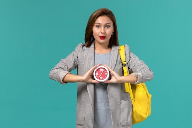 水色の壁に時計を保持している黄色のバックパックを身に着けている灰色のジャケットの女子学生の正面図