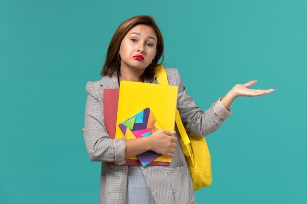 水色の壁にコピーブックとファイルを保持している黄色のバックパックを身に着けている灰色のジャケットの女子学生の正面図