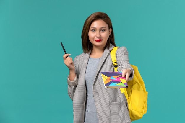 밝은 파란색 벽에 펜으로 카피 북을 들고 노란색 배낭을 입고 회색 재킷에 여성 학생의 전면보기