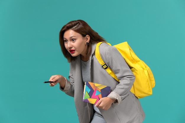 水色の壁にペンでコピーブックを保持している黄色のバックパックを身に着けている灰色のジャケットの女子学生の正面図