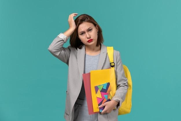 파란색 벽에 두통이있는 파일 및 카피 북을 들고 노란색 배낭을 착용하는 회색 재킷에 여성 학생의 전면보기