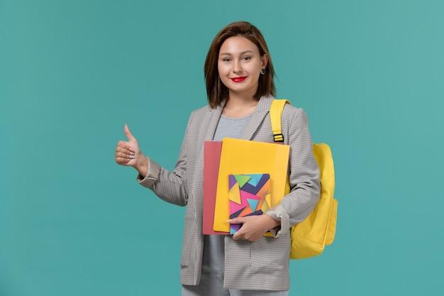 青い壁にファイルとコピーブックを保持している黄色のバックパックを身に着けている灰色のジャケットの女子学生の正面図
