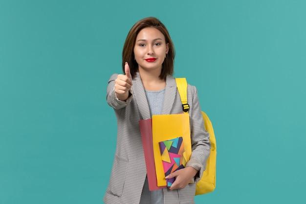 파란색 벽에 웃는 파일과 카피 북을 들고 노란색 배낭을 착용하는 회색 재킷에 여성 학생의 전면보기