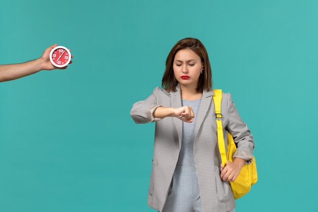Вид спереди студентки в серой куртке и желтом рюкзаке, смотрящей на ее запястье на голубой стене