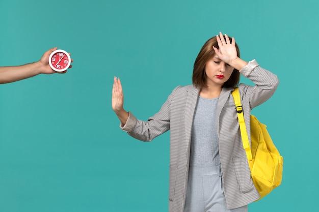 水色の壁に黄色のバックパックを身に着けている灰色のジャケットの女子学生の正面図