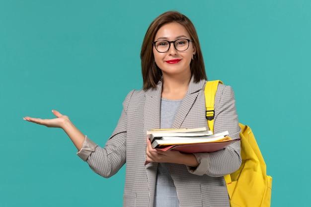 水色の壁に本を保持している灰色のジャケット黄色のバックパックの女子学生の正面図