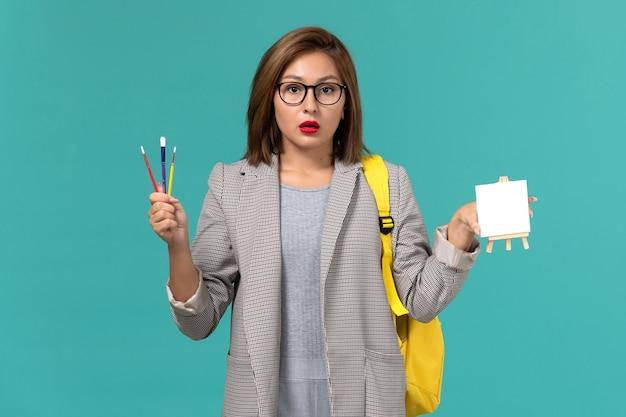 파란색 벽에 술과 이젤을 들고 회색 재킷 노란색 배낭 여성 학생의 전면보기
