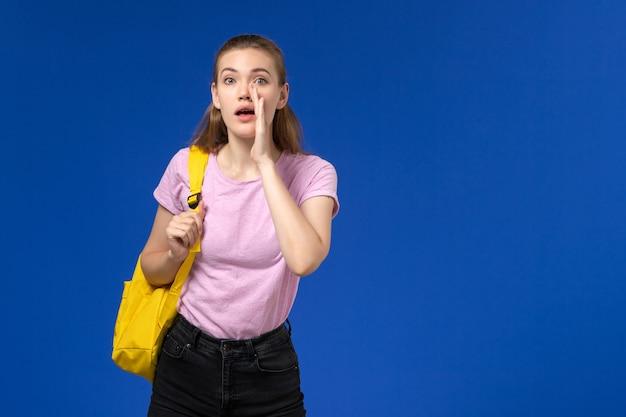 青い壁に叫んでいる黄色のバックパックとピンクのtシャツの女子学生の正面図