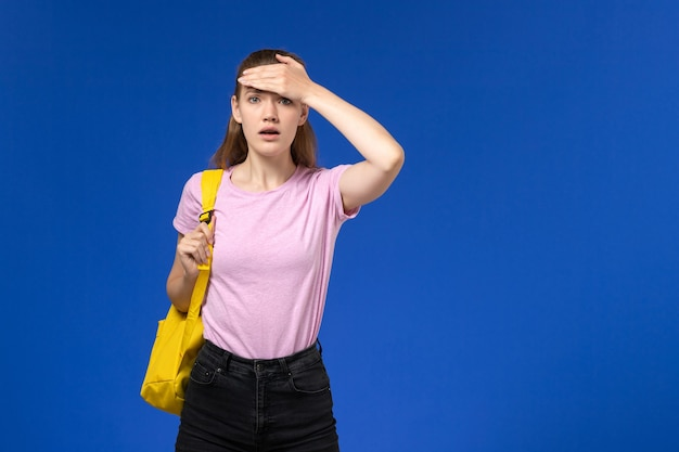 青い壁に黄色のバックパックの混乱した表情とピンクのtシャツの女子学生の正面図