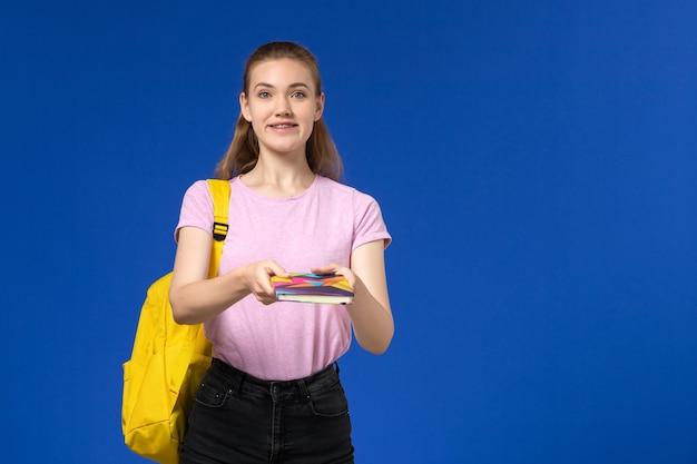 青い壁にコピーブックを保持している黄色のバックパックとピンクのtシャツの女子学生の正面図