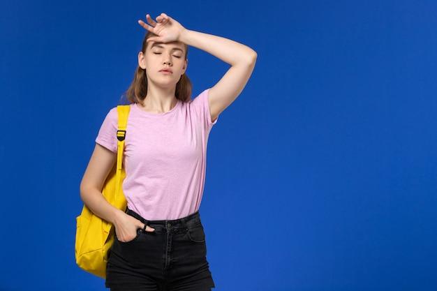 青い壁に黄色のバックパックとピンクのtシャツの女子学生の正面図