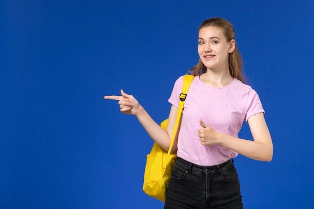 水色の壁に笑みを浮かべてポーズをとって黄色のバックパックとピンクのtシャツの女子学生の正面図
