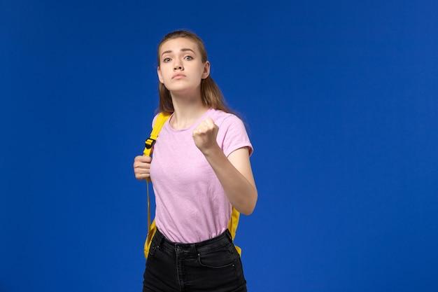 水色の壁にポーズと脅迫黄色のバックパックとピンクのtシャツの女子学生の正面図