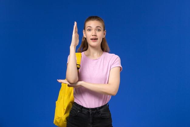Вид спереди студентки в розовой футболке с желтым рюкзаком, поднимающей руку на синей стене