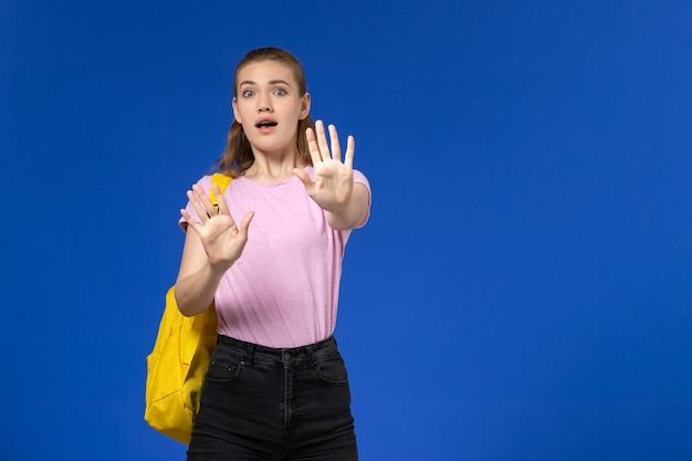 水色の壁に黄色のバックパック怖い表情とピンクのtシャツの女子学生の正面図