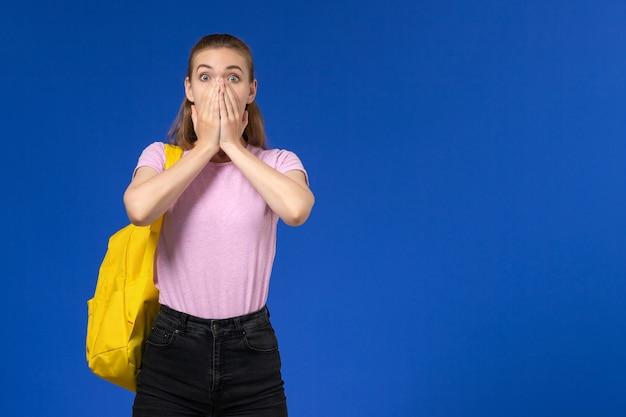 Вид спереди студентки в розовой футболке с желтым рюкзаком с шокированным выражением лица на голубой стене