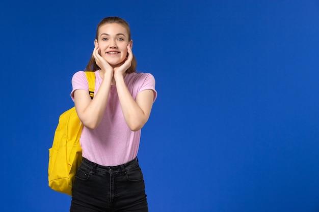 노란색 배낭 미소와 파란색 벽에 포즈와 분홍색 티셔츠에 여성 학생의 전면보기