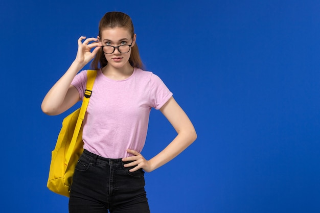 黄色のバックパックとピンクのtシャツの女子学生の正面図