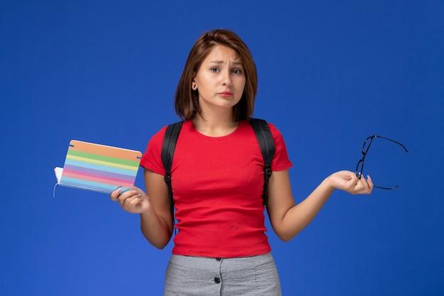 Вид спереди студентки в красной рубашке с рюкзаком, держащей тетрадь на голубой стене