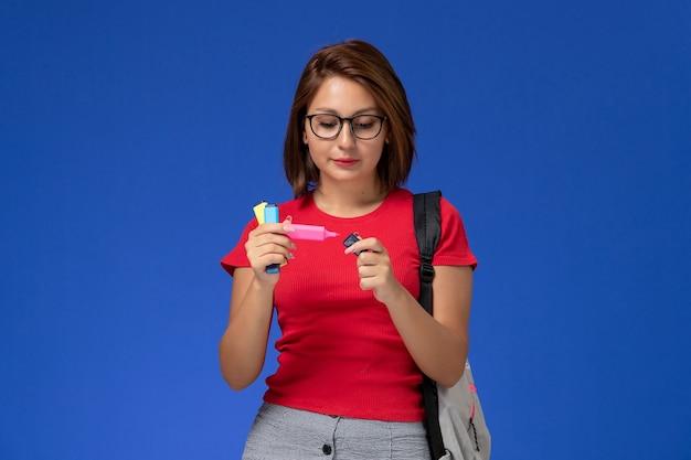 Вид спереди студентки в красной рубашке с рюкзаком, держащего фломастеры на синей стене