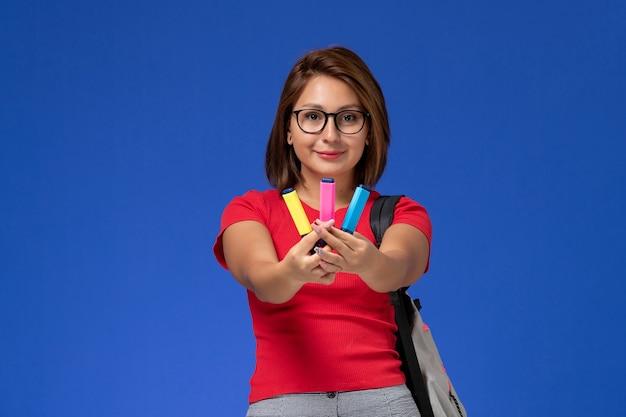 Вид спереди студентки в красной рубашке с рюкзаком, держащей фломастеры, улыбающейся на синей стене