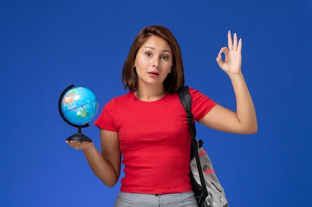 Вид спереди студентки в красной рубашке с рюкзаком, держащей маленький глобус на синей стене