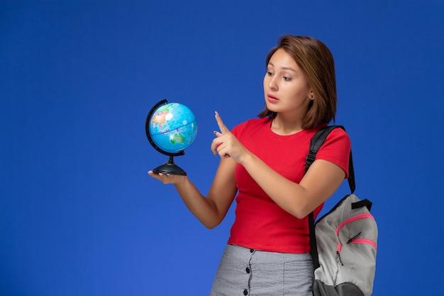 Вид спереди студентки в красной рубашке с рюкзаком, держащей маленький круглый глобус на синей стене