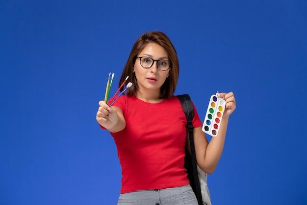 파란색 벽에 그림과 술을위한 페인트를 들고 배낭과 빨간 셔츠에 여성 학생의 전면보기