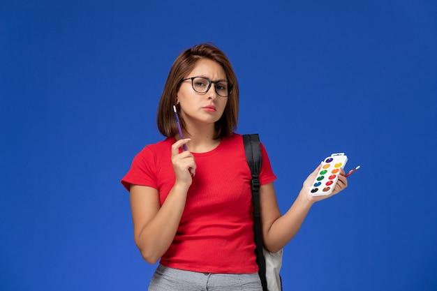 Вид спереди студентки в красной рубашке с рюкзаком, держащим краски для рисования и кисточки на синей стене