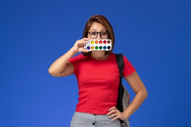 Вид спереди студентки в красной рубашке с рюкзаком, держащего краски для рисования на синей стене