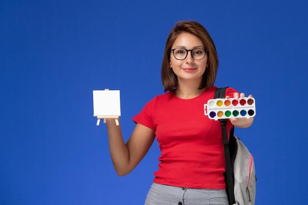 밝은 파란색 벽에 그리기위한 페인트를 들고 배낭과 빨간 셔츠에 여성 학생의 전면보기