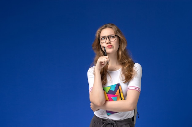 Вид спереди студентки в белой рубашке, держащей ручку и тетрадь, думая на синей стене
