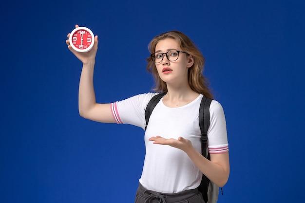 青い壁に時計を保持しているバックパックを身に着けている白いシャツの女子学生の正面図