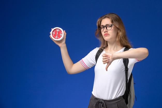 バックパックを身に着けて、青い壁に異なるサインを示す時計を保持している白いシャツの女子学生の正面図