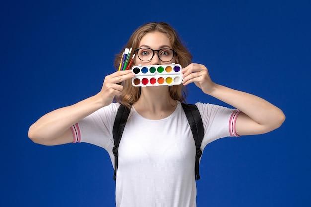 バックパックを身に着けて、青い壁にペンキとブラシを保持している白いシャツの女子学生の正面図