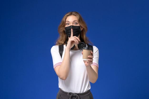 배낭 검은 마스크를 착용하고 파란색 벽에 커피를 들고 흰 셔츠에 여성 학생의 전면보기