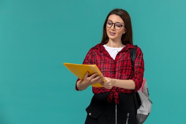 Вид спереди студентки, носящей рюкзак и держащей файлы на голубой стене