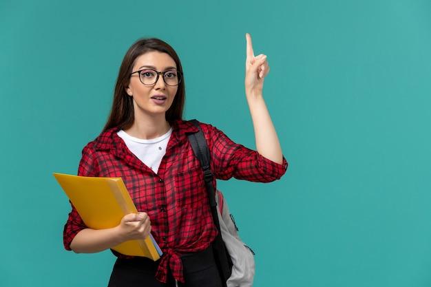 Вид спереди студентки в рюкзаке и держащей файлы, поднимающей палец на голубой стене