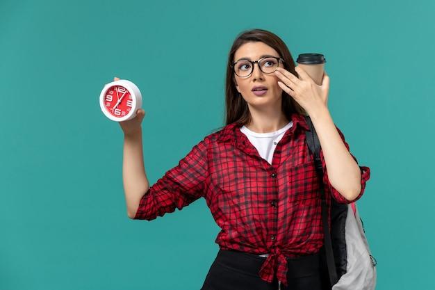 青い壁に時計とコーヒーを保持しているバックパックを身に着けている女子学生の正面図