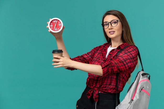 Вид спереди студентки в рюкзаке, держащей часы и кофе на синей стене