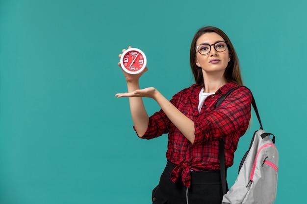 밝은 파란색 벽에 시계를 들고 배낭을 착용하는 여성 학생의 전면보기