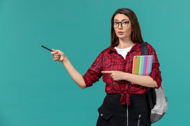 Вид спереди студентки в рюкзаке, держащей тетрадь и ручку на синей стене